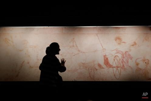 A schoolteacher explains the myth of Persephone in front of a replica of a mid-4th century BC wall painting of Hades abducting Persephone, whose original was found in a looted royal tomb, at the Vergina museum, northern Greece, onTuesday, Oct. 7, 2014. A similar scene has been discovered on a mosaic floor in a newly-excavated Macedonian tomb in Amphipolis, which has revived interest in ancient Greece's Macedonian dynasties. (AP Photo/Petros Giannakouris)