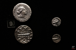 """Ancient Macedonian silver coins inscribed in Greek """"First of the Macedonians"""" and """"Macedonians"""" are seen in a display case at the archeological museum of Pella, Greece, onTuesday, Oct. 7, 2014. The city of Pella was the Macedonians' later capital, where the ancient Greek warrior-king Alexander the Great was born in 356 B.C. Excavations in recent decades there have uncovered extensive building remains, a rich mosaic floor believed to depict Alexander during a lion hunt, and large cemeteries. (AP Photo/Petros Giannakouris)"""