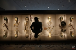 A visitor looks at a display of bronze armor and gold funerary masks and jewelry excavated in rich ancient Macedonian cemeteries at Aigai and Pella, in the archeological museum of Pella, northern Greece, on Tuesday, Oct. 7, 2014. The city of Pella was the Macedonians' later capital, where the ancient Greek warrior-king Alexander the Great was born in 356 B.C. Excavations in recent decades there have uncovered extensive building remains, a rich mosaic floor believed to depict Alexander during a lion hunt, and large cemeteries.(AP Photo/Petros Giannakouris)