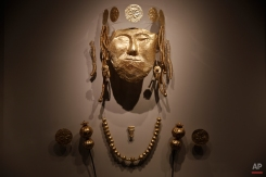 A funerary mask and other gold jewelry excavated in a rich ancient Macedonian cemetery is seen in the archeological museum of Pella, northern Greece, on Tuesday, Oct. 7, 2014. The city of Pella was the Macedonians' later capital, where the ancient Greek warrior-king Alexander the Great was born in 356 B.C. Excavations in recent decades there have uncovered extensive building remains, a rich mosaic floor believed to depict Alexander during a lion hunt, and large cemeteries.(AP Photo/Petros Giannakouris)