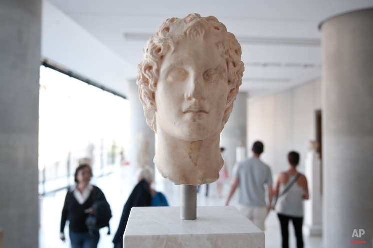 Visitors walk behind an ancient marble head of ancient Greek warrior-king Alexander the Great, displayed at the Acropolis museum in Athens, on Sunday, Oct. 12, 2014. Alexander the Great was one of the world's most successful military commanders, who enlarged his father's kingdom to include an empire stretching from modern Greece to India. During his youth, Alexander was tutored by the ancient Greek philosopher Aristotle until the age of 16. (AP Photo/Petros Giannakouris)