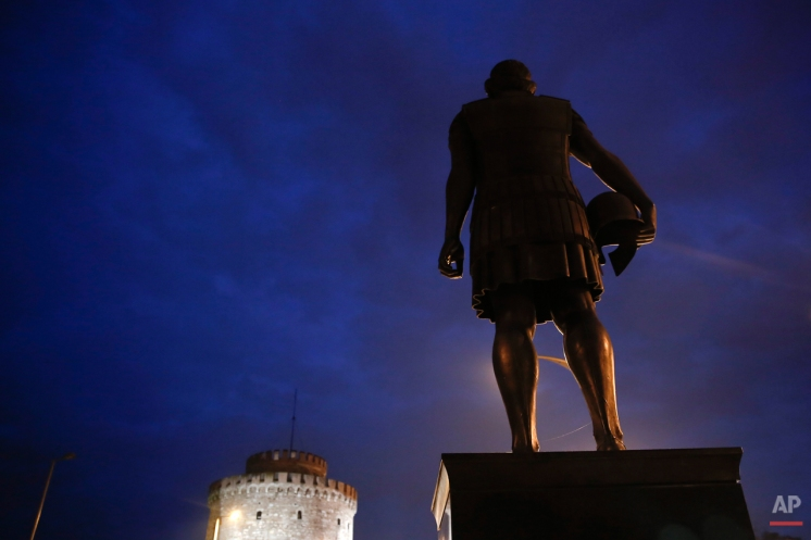 A modern bronze statue of ancient Greek King Phillip II of Macedon stands close to the lit-up mediaeval White Tower landmark in the northern port city of Thessaloniki, Greece on Wednesday, Oct, 8, 2014. Philip II reigned from 359 to 336 B.C. expanding his kingdom to include Greece's perennially squabbling city states. His son and successor, Alexander the Great, who distinguished himself in Philip's Greek campaigns, expanded Macedonian rule at the head of a Greek army, reaching as far as the borders of India. (AP Photo/Petros Giannakouris)