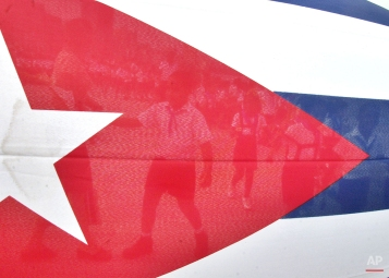 Children are seen through the Cuban flag while they walk to the Havana's Malecon to toss flowers into the ocean in commemoration of the anniversary of the death of the Cuban revolutionary Commander Camilo Cienfuegos, Thursday, Oct. 28, 2004 in Havana, Cuba. (AP Photo/Cristobal Herrera)