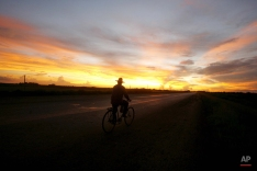 A man rides in his bicycle along an empty highway outside Havana, Cuba, Tuesday, Aug. 29 2006. (AP Photo/ Javier Galeano)