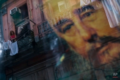 A Cuban woman hanging laundry on her balcony is seen reflected in a glass window decorated with a poster of Cuba's leader Fidel Castro in Old Havana, Cuba, Thursday, Dec. 27, 2007. (AP Photo/Dado Galdieri)