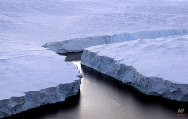 An enormous iceberg, right, breaks off the Knox Coast in the Australian Antarctic Territory on Jan. 11, 2008. Australia's CSIRO's atmospheric research unit has found the world is warming faster than predicted by the United Nations' top climate change body, with harmful emissions exceeding worst-case estimates. (AP Photo/Torsten Blackwood)