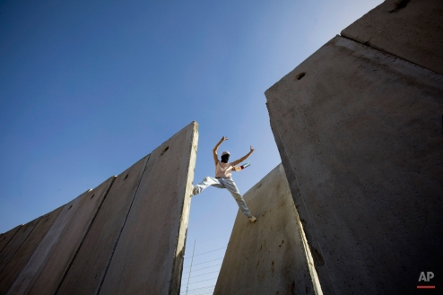 A Palestinian demonstrator gestures atop the separation barrier, moments after knocking down a segment of the concrete wall, during a protest against the barrier in the West Bank village of Nilin, near Ramallah, Friday, Nov. 6, 2009. (AP Photo/Bernat Armangue)