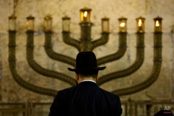 An Ultra-Orthodox Jewish man stands in front a menorah on the third eve of Hanukkah, at the Western Wall, Judaism's holiest site in Jerusalem's old city, Sunday, Dec. 13, 2009. (AP Photo/Sebastian Scheiner)