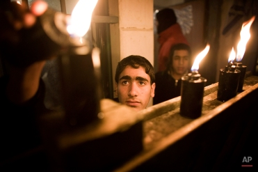 An Israeli Jewish settler lights a menorah on the seventh evening of Hanukkah in front of a house that Palestinians were evicted from two weeks ago in the east Jerusalem neighborhood of Sheikh Jarrah, Thursday, Dec. 17, 2009. (AP Photo/ Tara Todras-Whitehill)