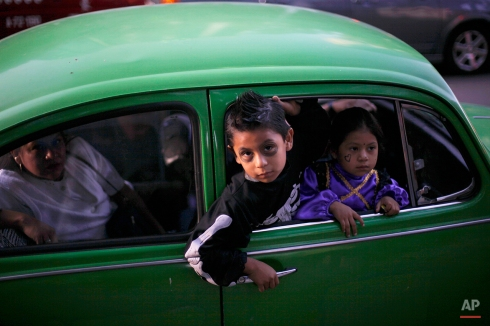 Children wearing Halloween costumes peers from a car on Day of the Dead in Mexico City, Tuesday Nov. 2, 2010. Mexicans celebrate Day of the Dead to honor deceased loved ones, a tradition that coincides with All Saints Day and All Souls Day on Nov. 1 and 2. (AP Photo/Alexandre Meneghini)