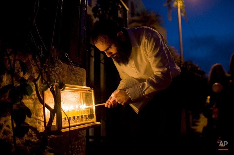 A Jewish man lights candles on the eve of the last night of Hanukkah, in Jerusalem, Wednesday, Dec. 8, 2010. The Jewish festival of light, an eight-day commemoration of the Jewish uprising in the second century B.C. against the Greek-Syrian kingdom, which had tried to put statues of Greek gods in the Jewish Temple in Jerusalem, started last Wednesday. (AP Photo/Tara Todras-Whitehill)