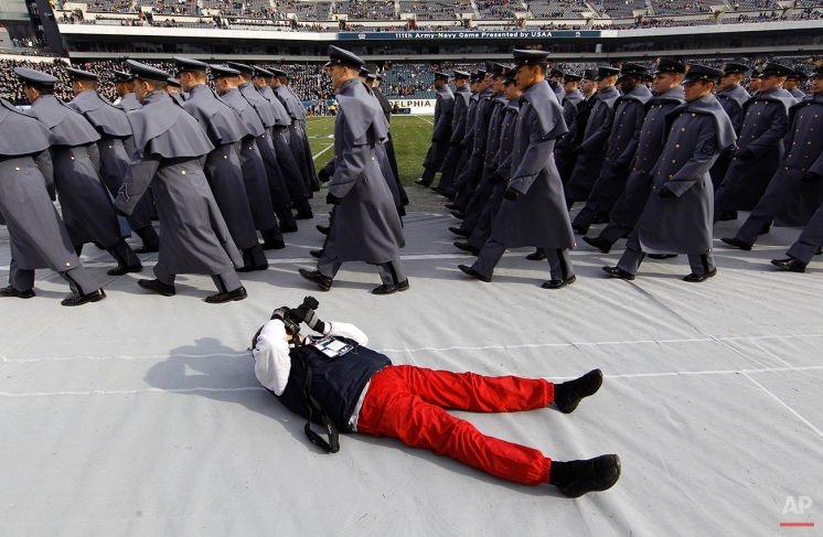 A photographer lies on the ground to photograph Army Cadets marching by before an NCAA college football game against Navy, Saturday, Dec. 11, 2010, in Philadelphia. (AP Photo/Matt Slocum)