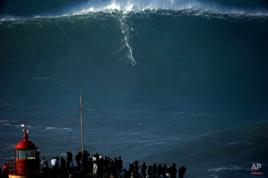 A surfer rides a huge wave during a tow-in surfing session at the Praia do Norte or North beach, in Nazare, Portugal, Thursday, Dec, 11, 2014. The beach has become a famous break point for big wave riders around the world. (AP Photo/Francisco Seco)