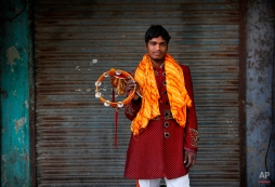 In this Friday, Nov. 28, 2014, photo, Salim, 23, from Agra, some 209 kilometres (130 miles) from Delhi, a members of Master Band, an Indian brass band specialized in playing weddings, poses for a portrait in New Delhi. (AP Photo/Manish Swarup)