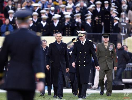 President Barack Obama, center, is escorted across the field from the Navy side to the Army side during the second half of the 112th edition of the annual Army vs. Navy NCAA college football game at FedEx Field in Landover, Md., Saturday, Dec. 10, 2011. (AP Photo/Manuel Balce Ceneta)