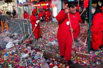 Workers begin cleaning up the aftermath of Time Square's New Years Eve celebrations, Sunday, Jan. 1, 2011, in New York. Revelers erupted in cheers amid a confetti-filled celebration in New York's Times Square to welcome in the new year, part of star-studded celebrations and glittering fireworks displays around the world to usher in 2012. (AP Photo/John Minchillo)
