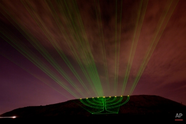Laser beams creating the image of a large lit Hanukkah menorah are projected on the Hiriya landfill, a former waste disposal site, now called the Ariel Sharon Park, near Tel Aviv, Israel, on the second eve of Hanukkah, Wednesday, Dec. 21, 2011. (AP Photo/Ariel Schalit)