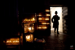 An Ultra Orthodox Jewish walks past lit candles during the Jewish holiday of Hanukkah in Jerusalem's Mea Shearim neighborhood, Monday, Dec. 26, 2011. The Jewish festival of light, an eight-day commemoration of the Jewish uprising in the second century B.C. against the Greek-Syrian kingdom, which had tried to put statues of Greek gods in the Jewish Temple in Jerusalem, started last Tuesday. (AP Photo/Bernat Armangue)