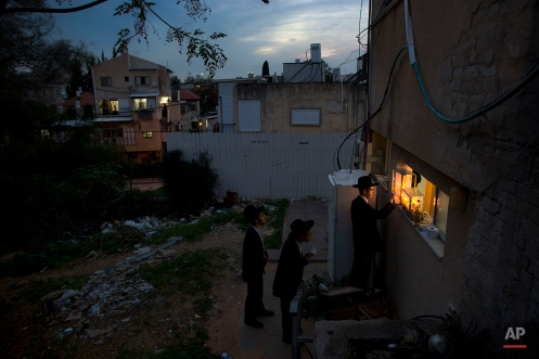 An ultra-Orthodox Jewish man lights candles during the Jewish holiday of Hanukkah in the ultra-Orthodox city of Bnei Brak near Tel Aviv, Israel, Thursday, Dec. 18, 2014. (AP Photo/Oded Balilty)