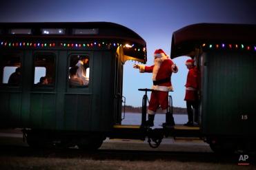 """A man portraying Santa Claus moves between cars while greeting passengers during a Polar Express holiday train ride to the """"North Pole"""" on the Maine Narrow Gauge Railroad, Friday, Dec. 19, 2014, in Portland, Maine. The Polar Express is the largest annual fundraiser for the railroad's museum. (AP Photo/Robert F. Bukaty)"""