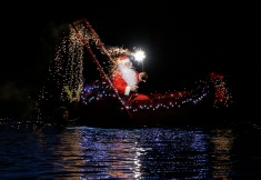 A man dressed as Santa Claus lights flares as he sits on a boat in Imperia, near Genoa, Italy, Wednesday, Dec. 24, 2014. (AP Photo/Antonio Calanni)