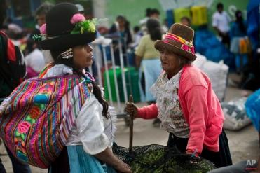 Women buy vegetables at a popular market in Yungay, Peru, Tuesday, Dec. 2, 2014. (AP Photo/Rodrigo Abd)