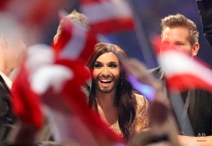 """Singer Conchita Wurst, representing Austria who performed the song """"Rise Like a Phoenix"""", listens as points are announced during the judging at the final of the Eurovision Song Contest in the B&W Halls in Copenhagen, Denmark, Saturday, May 10, 2014. (AP Photo/Frank Augstein)"""