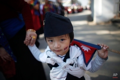 """A young Nepalese Gurung boy holds a flag of Nepal and walks in a parade to mark their New Year know as """"Tamu Loshar"""" in Katmandu, Nepal, Tuesday, Dec 30, 2014. The indigenous Gurungs, also known as Tamu, are celebrating their new year, welcoming the year of the Sheep. (AP Photo/Niranjan Shrestha)"""