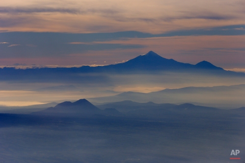 Pico de Orizaba, or Citlaltepetl mountain, rises above the morning mist as seen from a Mexican Navy aircraft on a volcano monitoring mission in Mexico, Tuesday, July 23, 2013. Pico de Orizaba is Mexico's highest peak and the third highest in North America. (AP Photo/Dario Lopez-Mills)
