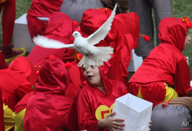 """In this Nov. 30, 2014 photo, children dressed as """"El Chapulin Colorado"""" and """"El Chavo del Ocho"""" characters, release white doves during the memorial service of Mexican comedian Roberto Gomez Bolanos at the Azteca stadium the in Mexico City. The iconic Mexican comedian who also wrote and played the boy television character """"El Chavo del Ocho"""" and """"El Chapulin Colorado,"""" defined a generation for millions of Latin American children, died Friday at age 85. (AP Photo/Marco Ugarte)"""