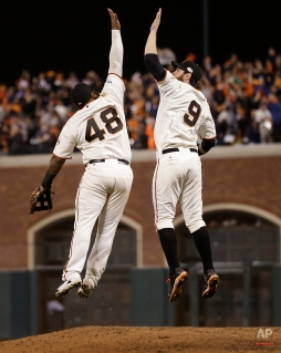 San Francisco Giants Pablo Sandoval, left, leaps up to high five Brandon Belt after defeating the Kansas City Royals 11-4 in Game 4 of baseball's World Series Saturday, Oct. 25, 2014, in San Francisco. The Giants tied the series 2-2. (AP Photo/Matt Slocum)