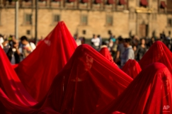 Protestors draped in a giant red cloth to represent blood, march during a demonstration in Mexico City, Monday, Dec. 1, 2014. Protesters marched in several cities in Mexico on Monday to mark the second anniversary of President Enrique Pena Nieto's administration and demand the government find 43 students who disappeared at the hands of police. (AP Photo/Rebecca Blackwell)