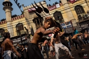 A young Indian Shiite Muslim flagellates himself during a procession to mark Ashoura in New Delhi, India, Tuesday, Nov. 4, 2014. Shiites mark Ashoura, the tenth day of the month of Muharram, to commemorate the Battle of Karbala when Imam Hussein, a grandson of Prophet Muhammad, was killed. (AP Photo/Bernat Armangue)