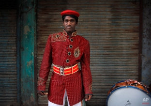 In this Monday, Nov. 3, 2014, photo, Shivraj 26, from Lalitpur, some 547 kilometres (341 miles) from Delhi, a members of Master Band, an Indian brass band specialized in playing weddings, poses for a portrait in New Delhi. Dressed in faded military-style uniforms or long silken tunics and turbans, brass bands playing the latest Bollywood tunes have long been a must-have at any Indian wedding. (AP Photo/Manish Swarup)