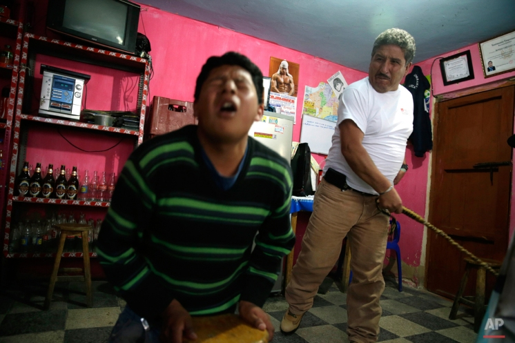 """In this June 7, 2014 photo, 17-year-old Miguel Chusqui grimaces in pain as he is lashed by a """"rondero,"""" a member of a citizen vigilante group known as a """"ronda urbana,"""" or urban patrol, in Cajamarca, Peru. Chusqui was sentenced to five lashes for stealing a laptop. Rondas only handle cases that authorities consider minor, settling property and debt disputes, family quarrels and marital infidelities. If a felony is committed, the rondas turn the transgressor over to police. The harshest sentence they administer, they say, is banishment. (AP Photo/Martin Mejia)"""