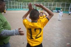 "In this Thursday, Nov. 27, 2014 photo, Roberto Castellanos, enters the soccer pitch during a game of the ""Goal for Life"" soccer project at El Progreso neighborhood in Tegucigalpa, Honduras. (AP Photo/Esteban Felix)"