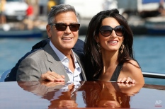 George Clooney, left, and Amal Alamuddin arrive in Venice, Italy, Friday, Sept. 26, 2014. Clooney, 53, and Alamuddin, 36, are expected to get married this weekend in Venice. (AP Photo/Luca Bruno)