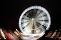 In this photo taken with a slow shutter speed, the big wheel is illuminated as part of Christmas lights on the Champs Elysees, in Paris, Thursday, Dec. 4, 2014. (AP Photo/Francois Mori)