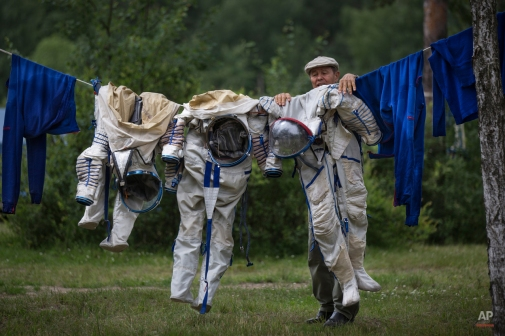 An employee of the Russian Space Training Center hangs out space suits to dry of Russian cosmonaut Anatoly Ivanishin, NASA's U.S. flight engineer Kathleen Rubins and Japanese space agency's flight engineer Takuya Onishi after their undergoing training near in Noginsk, 60 km (38 miles) east of Moscow, Russia, Wednesday, July 2, 2014. The training was intended to simulate the capsule landing on water. (AP Photo/Alexander Zemlianichenko)