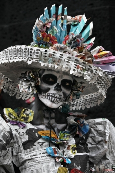 """In this Nov. 1, 2014 photo, a woman dressed as the iconic Mexican """"Catrina"""" poses for photographers as she gathers with other women in costume in an attempt to set a record for the most Catrinas in one place during Day of the Dead celebrations in Mexico City. The figure of a skeleton wearing an elegant broad-brimmed hat was first done as a satirical engraving by artist Jose Guadalupe Posada sometime between 1910 and his death in 1913. (AP Photo/Marco Ugarte)"""