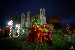 Two women dressed as elves entertain people in a Christmas village set up in the medieval castle of Obidos, central Portugal, Wednesday, Dec. 17, 2014. (AP Photo/Francisco Seco)