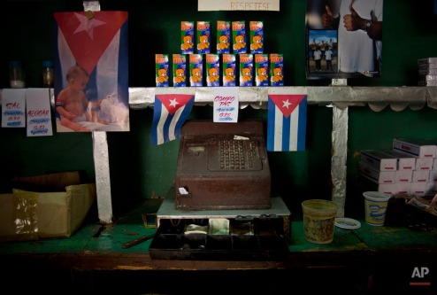 Cuban flags are placed next to an old cash register in state bodega in Havana, Cuba, Thursday, Dec. 18, 2014. After a half-century of Cold War acrimony, the United States and Cuba abruptly moved on Wednesday to restore diplomatic relations, a historic shift that could revitalize the flow of money and people across the narrow waters that separate the two nations. (AP Photo/Ramon Espinosa)