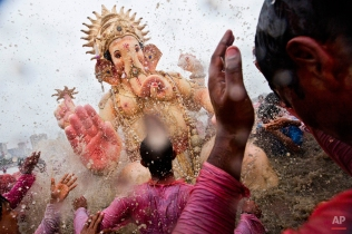 Indian Hindu devotees splash water on a large statue of the elephant-headed Hindu God Ganesha before immersing it in the Arabian Sea on the final day of the festival of Ganesha Chaturthi in Mumbai, India, Monday, Sept. 8, 2014. (AP Photo/Bernat Armangue)