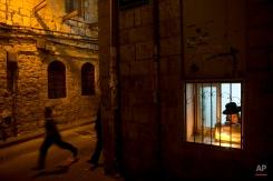 An ultra-Orthodox Jewish man lights candles during the Jewish holiday of Hanukkah in Jerusalem's Mea Shearim neighborhood Sunday, Dec. 21, 2014. (AP Photo/Oded Balilty)