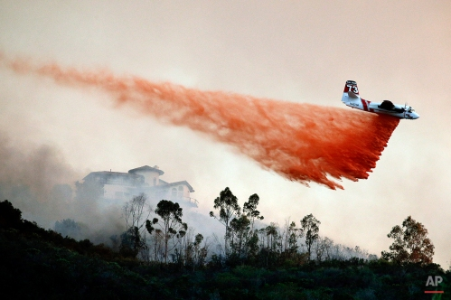 A plane drops fire retardant over a hot spot on Wednesday, May 14, 2014, in San Marcos, Calif. Flames engulfed suburban homes and shot up along canyon ridges in one of the worst of several blazes that broke out Wednesday in Southern California during a second day of a sweltering heat wave, taxing fire crews who fear the scattered fires mark only the beginning of a long wildfire season. (AP Photo)