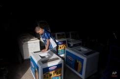 In this Tuesday, Nov. 25, 2014 photo, Roberto Castellanos assembles an ice cream cart at a bicycle repair ship in Tegucigalpa, Honduras. (AP Photo/Esteban Felix)