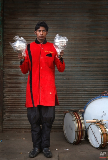 In this Monday, Nov. 3, 2014, photo, Kapil Singh, 19, from Jhansi, some 443 kilometres (276 miles) from Delhi, a members of Master Band, an Indian brass band specialized in playing weddings, poses for a portrait in New Delhi. (AP Photo/Manish Swarup)