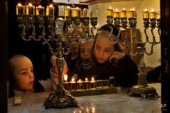 Members of the Kraus family, a Jewish ultra-orthodox family, light candles during the Jewish holiday of Hanukkah in Jerusalem's Mea Shearim neighborhood, Monday, Dec. 2, 2013. (AP Photo/Bernat Armangue)