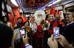 Subway commuters take cell phone pictures of performers dressed as Santa Claus, Mrs. Claus and elves inside a train car in Sao Paulo, Brazil, Friday, Dec. 5, 2014. This Santa says he'll ride the city's subway trains during December to celebrate the Christmas season. (AP Photo/Andre Penner)