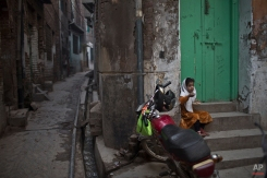A girl, eats by the doorway of her home, near the house of Pakistani student Nasrullah Abdullah, 17, who was killed in last Tuesday's Taliban attack on a military-run school, in Peshawar, Pakistan, Thursday, Dec. 18, 2014. (AP Photo/Muhammed Muheisen)